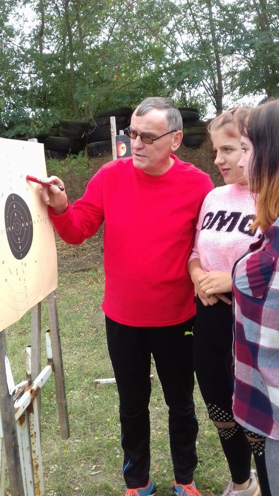 Dariusz Kufel objaśnia młodzieży punktację na tarczy.